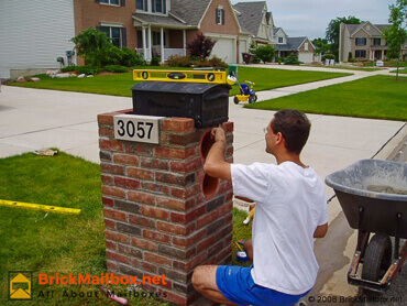 Leveling plastic mailbox with stone number in place