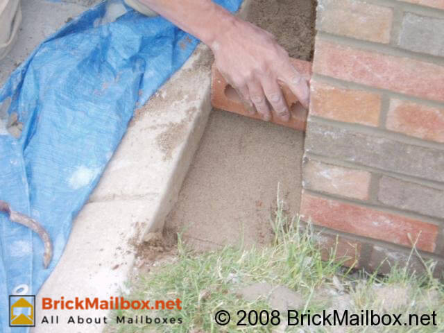 Dig a hole right in front of the brick mailbox, fill with sand and then level.